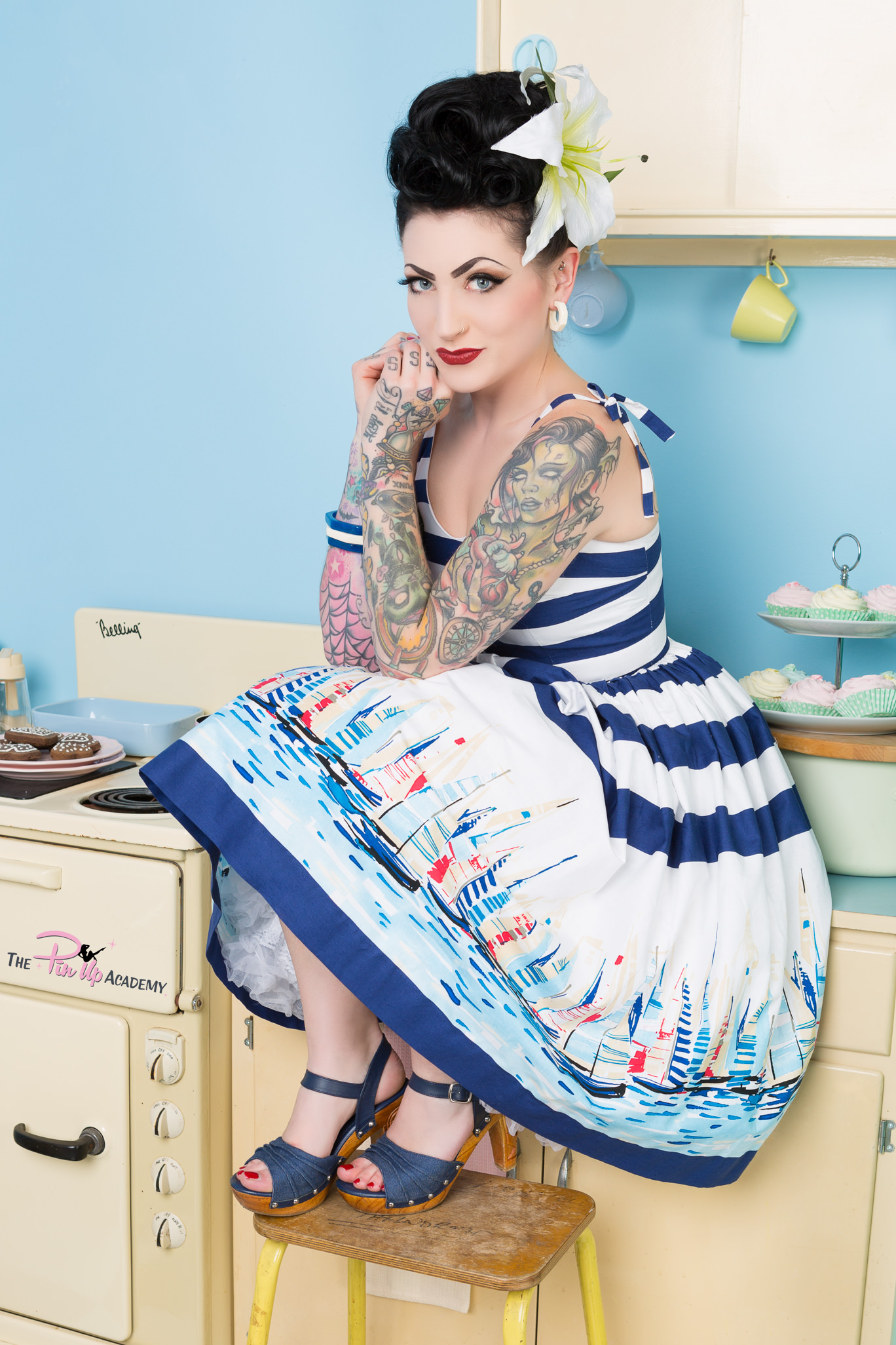pinup model in nautical dress sat in kitchen